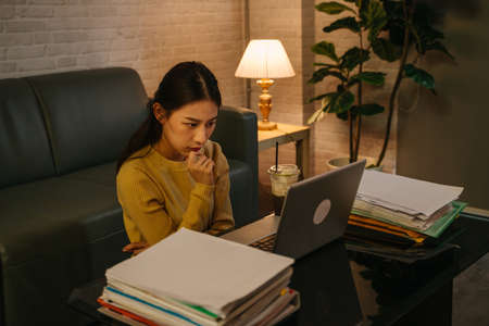 Tired young Asian female businesswoman thinking with hands on chin while staring at laptop screen with office working files on table during late night at home