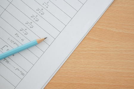 pencil and sheet of paper with maths-formulas