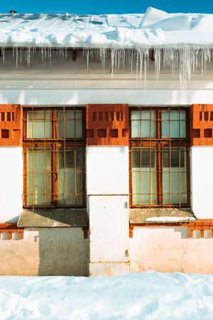 redbrick: Small building with icicles and snow in Winter, Moscow, Russia