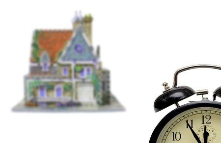 makelaardij: huis met een alarm-klok ingesteld vijf-twaalf geïsoleerd op witte achtergrond Stockfoto