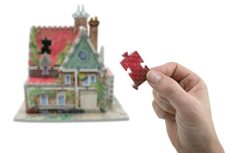 huis met de hand en de ontbrekende puzzel-delige geïsoleerd op witte achtergrond Stockfoto