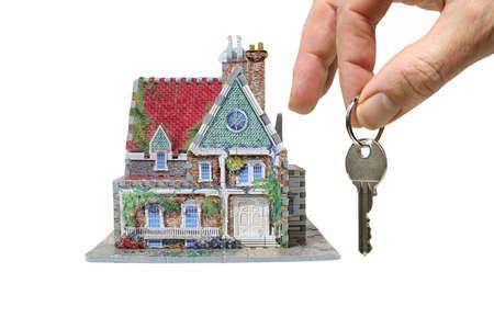 makelaardij: huis met de hand en de toetsen geïsoleerd op witte achtergrond Stockfoto