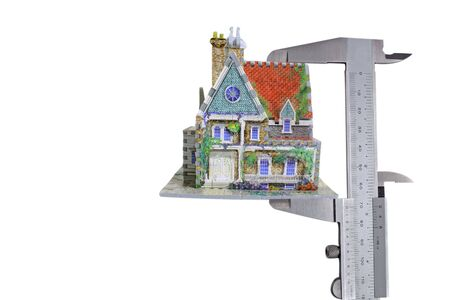 house withcalipers measurement-tool isloated on white background photo