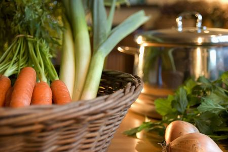 vegetables in a basket  with pan on kitchen-table in kitchen