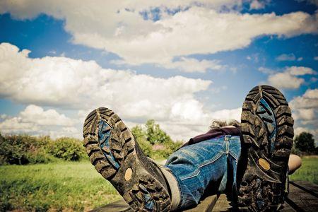 huella pie: caminante toma un descanso en un verano en la parte inferior de day.Focus excursiones-boots.Personal edici�n Velvia Foto de archivo