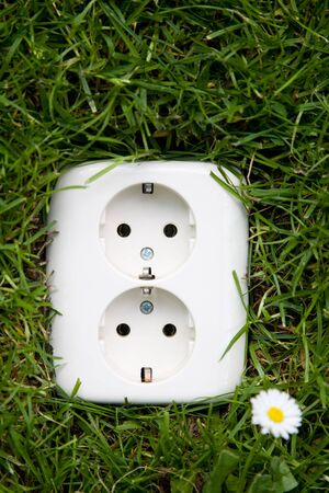 grounded plug: energy concept outllet in grass