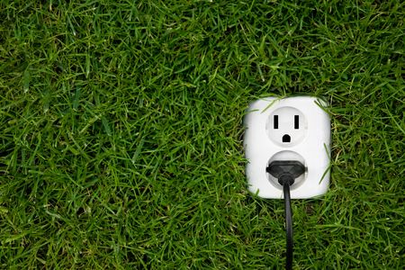 energy saving: energy concept outllet in grass