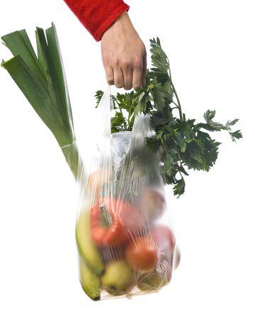 hand van een vrouw die een kruidenier-tas met groenten en fruit Stockfoto