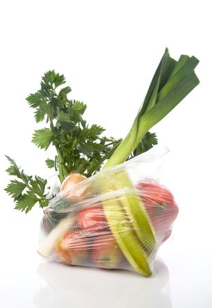 plastic bags: grocery-bag with vegetables and fruits isolated on a white background with a soft reflection Stock Photo