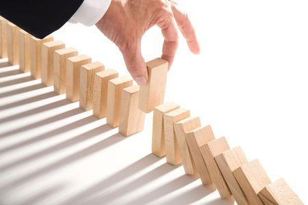 interventie: dominospel geïsoleerd op wit als een abstract concept Stockfoto