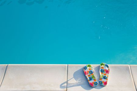 swimmingpool: two flip-flops with flowers near the swimming-pool in the morning sun