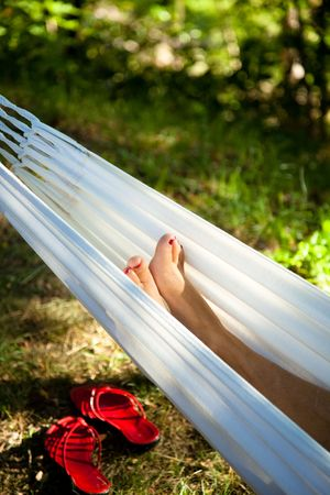 feet of a mature woman in a hammock at sunset