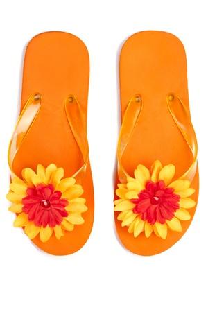 Oranje slippers met bloemen op een witte achtergrond