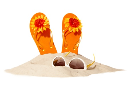 flip-flops and sunglasses on a sunny pile of sand Stock Photo