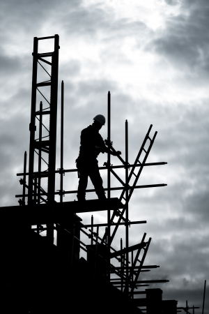 construction project: silhouette of construction worker on scaffold