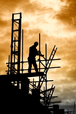 buildingsite: silhouette of construction worker on scaffold