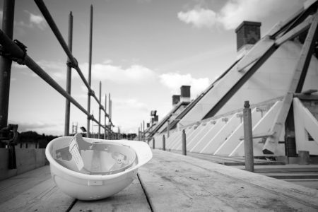 empty building site with left helmet on scaffold. Concept crisis building industry Foto de archivo
