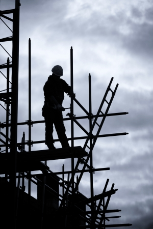 buildingsite: silhouette of construction worker on scaffolding, Blue toned Stock Photo