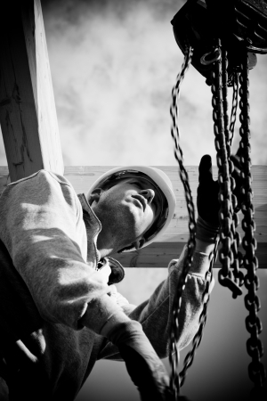 construction safety: construction worker  at work with wooden  roof construction Stock Photo