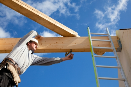 home builder: carpenter at work with wooden  roof construction