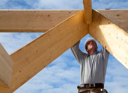 Timmerman aan het werk met houten dakconstructie Stockfoto - 17823813
