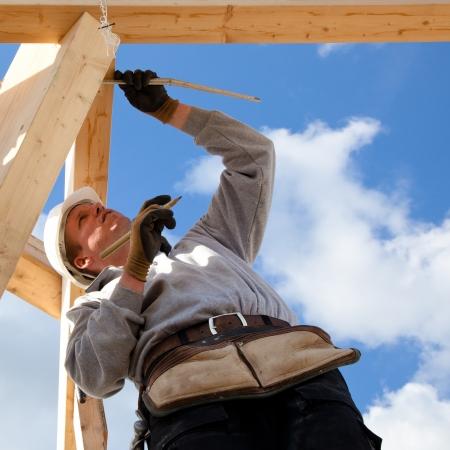 dakdekker aan het werk met het meten van de bouw