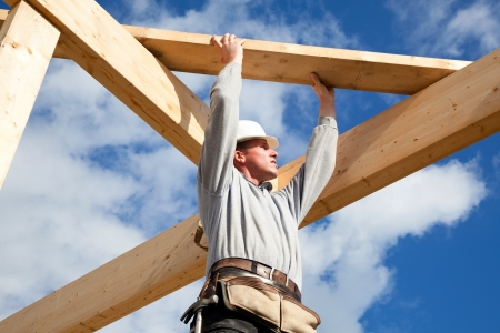 wooden house: workman at work with wooden  roof construction Stock Photo