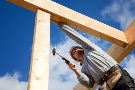 builder at work with wooden  roof construction Stock Photo