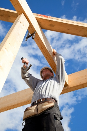 new site: construction worker at work with wooden  roof construction