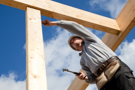 home construction: construction worker at work with wooden  roof construction