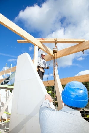 construction workers at work with wooden  roof construction of a new home Stock Photo