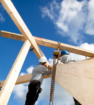 timber frame: construction workers making a wooden  roof construction