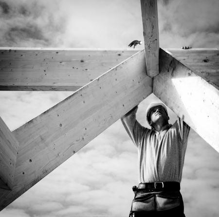 manual worker: builder at work with wooden  roof construction Stock Photo