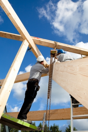 construction workers making a wooden  roof construction photo