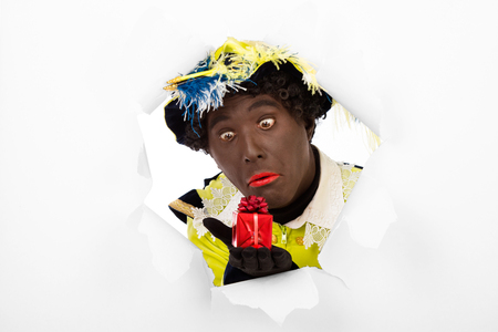 advertize: zwarte piet   black pete  Looking through hole  typical Dutch character part of a traditional event celebrating the birthday of Sinterklaas in december