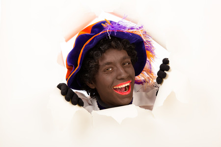saint nicolaas: zwarte piet   black pete  Looking through hole  typical Dutch character part of a traditional event celebrating the birthday of Sinterklaas in december
