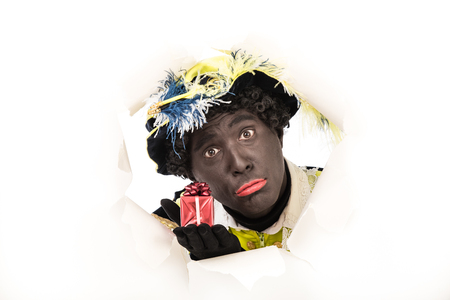 zwarte piet   black pete  Looking through hole  typical Dutch character part of a traditional event celebrating the birthday of Sinterklaas in december photo