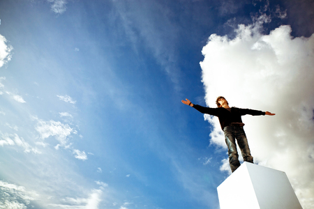 Teenager with his arms wide open looking into a blue sky photo