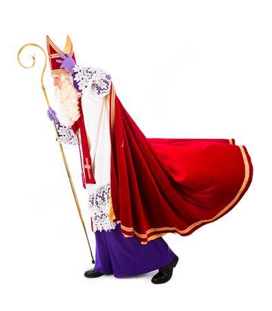 sinterklaas: Sinterklaas holding hat in windy weather  isolated Stock Photo
