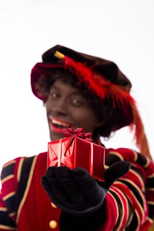 zwarte: smiling zwarte piet ( black pete)  with gift . typical Dutch character part of a traditional event celebrating the birthday of Sinterklaas (Santa Claus) in december
