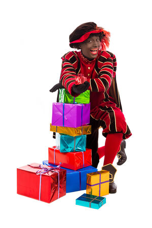 nicolaas: zwarte piet   black pete   with gift   typical Dutch character part of a traditional event celebrating the birthday of Sinterklaas  Santa Claus  in december