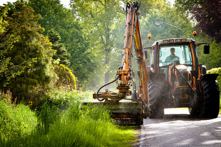 mowing grass: mowing grass shoulder with tractor Stock Photo