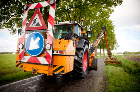mowing grass shoulder along road with tractor