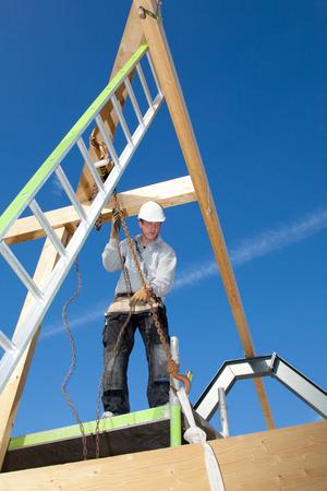 bouwvakker aan het werk met een lier op de dakconstructie photo