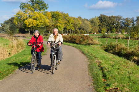 Senior man and woman on bicycles on a dutch countryroad 스톡 콘텐츠