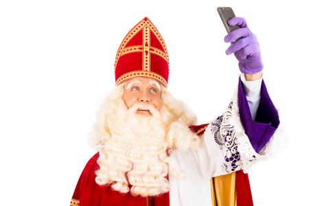 Sinterklaas maken Selfie met mobiel. geïsoleerd op een witte achtergrond. Nederlandse karakter van de Kerstman