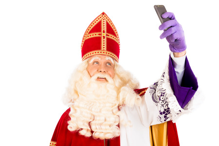 nicolaas: Sinterklaas  making selfie with mobile. isolated on white background. Dutch character of Santa Claus