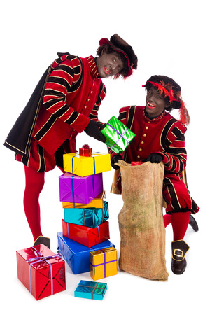 sint nicolaas: zwarte piet ( black pete)  with gift . typical Dutch character part of a traditional event celebrating the birthday of Sinterklaas (Santa Claus) in december