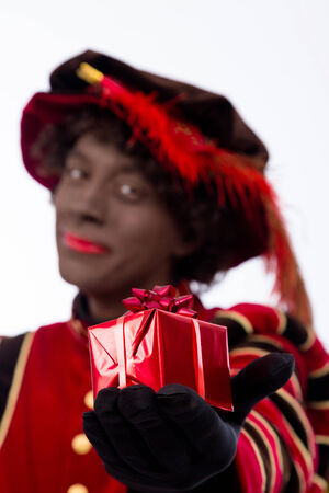 pieten: zwarte piet ( black pete)  with gift . typical Dutch character part of a traditional event celebrating the birthday of Sinterklaas (Santa Claus) in december