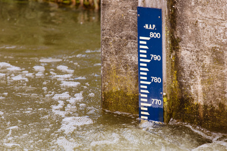 depth measurement: water level meter on a concrete wall in river